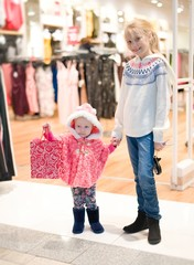 Kids doing shopping in the mall , shopping center .