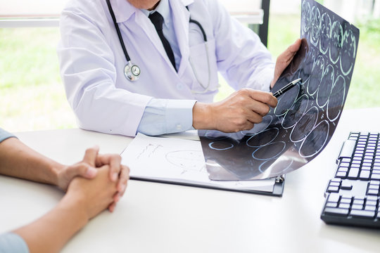 doctor analyzing a scan or x-ray film or explains a CT scan thoughtful expressions method talking to patient treatment on brain to an anomaly.