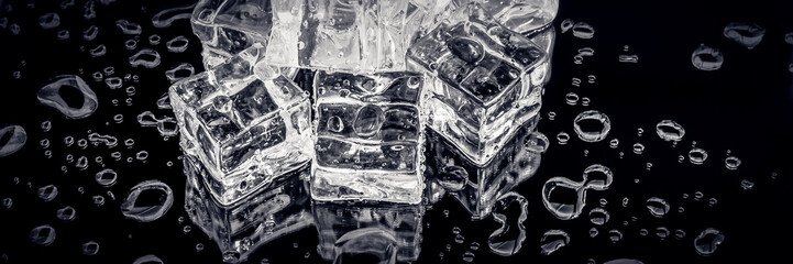 Ice cubes among water splashes on black background.