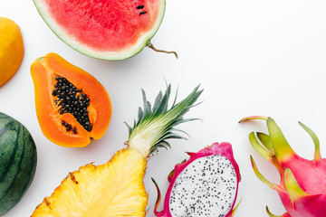 Flat lay tropical fruit layout made of dragon fruit, watermelon, papaya and pineapple on a white background, creative summer food concept Wall mural