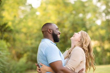 Loving mixed race couple hugging and laughing.