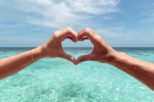 heart shape with a male and female hand. Clear blue water as background. Freedom in paradise concept