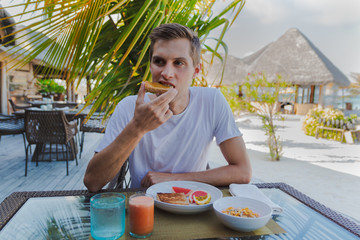young man on holiday in a tropical island eating a healthy breakfast