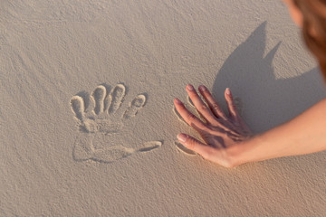 young woman doing Handprints in white sand