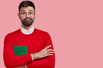 Indoor shot of handsome man with thick stubble, presses lips, keeps arms folded, carries green notebook for writing notes, wears red jumper, has attentive gaze, isolated over pink background