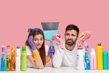 Unhappy couple do cleaning at home together, have fatigue expressions, use cleaning products and supplies, pose at table, isolated over pink background. Husband and wife bring house to order