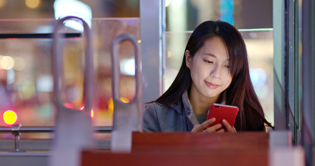 Woman use of mobile phone on tram at night