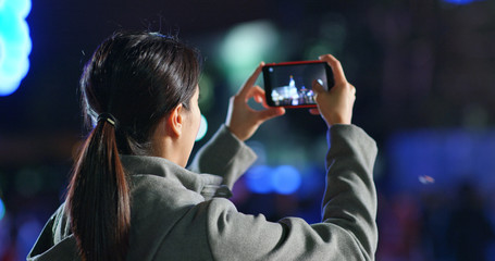 Woman take photo on smart phone in the street at night