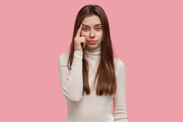 Serious good looking woman looks confidently at camera, keeps finger on temples, raises eyebrow, has long dark hair, dressed in casual clothes, models against pink wall. Daydreaming and thinking
