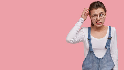Photo of puzzled woman scratches head in bewilderment, thinks about finding right solution, wears trendy sarafan, round spectacles, models over pink background with free space for information