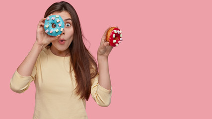 Surprised emotive dark haired lady covers face with tasty doughnuts, has surprised expression, dressed casually, isolated over pink studio wall with free space for your information. Delicious snack