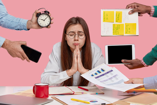 Wishful college student keeps hands in praying gesture, believes in good fortune, closes eyes, prepares task in economics, asks God dreams come true, isolated over pink background, works overtime