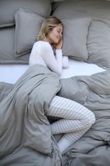 Junge Frau schlafend in ihrem Bett