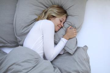 Frau kuschelt sich lächelnd in ihrem Bett ein