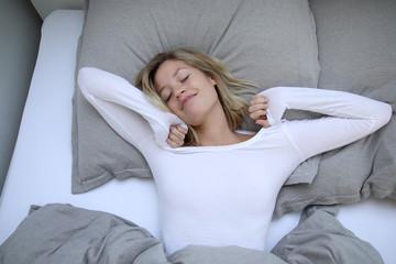 Frau liegt in ihrem Bett und streckt sich