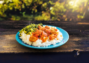 Creole dish - Fish cari with rice and fricassee of brede in a blue dish on a wooden picnic table with blur background - Cari thon avec fricassé de brède