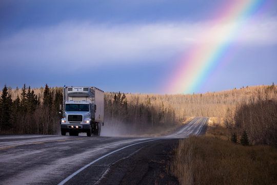 Cube semit truck on wet asphalt road with colorful rainbow over late fall forest landscape after rain in Yukon Territory, YT, Canada