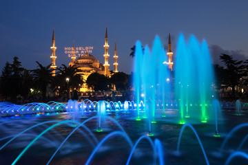 """Blue Mosque with the fountain in the foreground, famous tourist destination in Istanbul, Turkey, on the first day of Ramadan with illuminated message meaning """"Welcome the sultan of eleven months""""."""