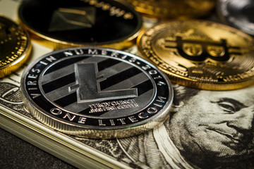 Bitcoin and other cryptocurrency coins on packs of dollars