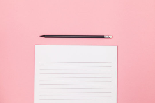 Blank page in a line with black pencil. Plans and goals for the year. Freelancer workplace concept. Top view with copy space for input the text. Flat lay, colored pink background.