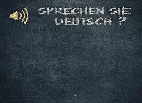 Sprechen Sie Deutsch - Do you speak German question handwritten with white chalk on a blackboard