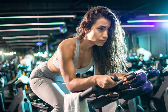 Beautiful fit woman cycling during workout on stationery bike for burning calories in the spinning studio.