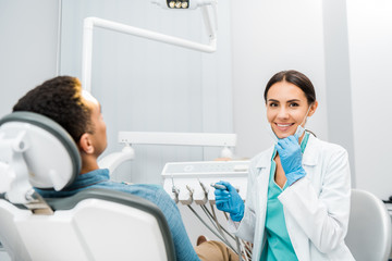 cheerful dentist holding drill and smiling near african american patient