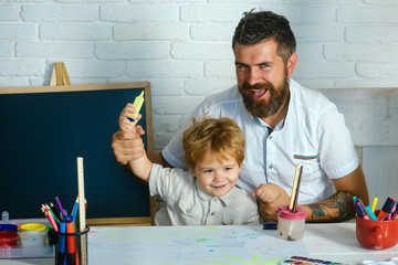 Art for children. Bearded adult father teaches to draw little son in studio. Boy and man draw picture. Creative education and art, development in kindergarten. Childhood with parents talented teacher