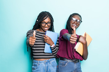 Young afro american student girls show thumbs up and holding netobooks isolated on pastel blue...