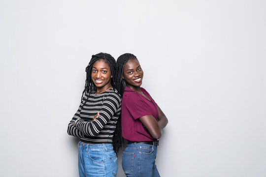 African two women standing back to back not speaking to each other on white background.