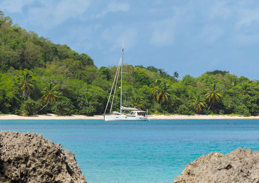 Catamaran moored in tropical bay with exotic beach in background