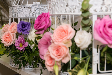 Various bridal flower heads in vintage ornate bird cage as bloom decoration at a wedding reception