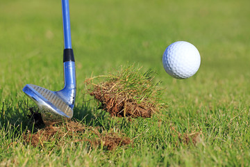 chipping a golf ball out of the rough grass with a big divot