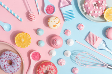 Kitchen utensils and tools, pastries and sweets on a pink and blue background. Top view. Copy space. Wall mural