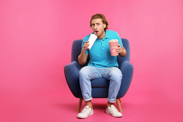 Emotional man with popcorn and beverage sitting in armchair during cinema show on color background Wall mural