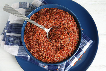 Bowl with uncooked red rice and spoon on white table, top view
