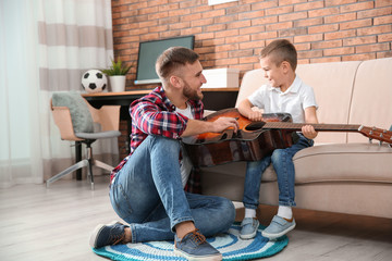 Father teaching his little son to play guitar at home