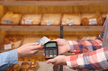 Woman using credit card for terminal payment in bakery, closeup