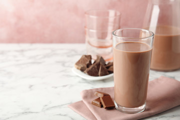 Glass with tasty chocolate milk on marble table, space for text. Dairy drink