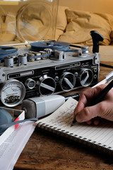 Female hand writing on notebook with tape recorder and microphone, journalist transcribing an interview, close shot