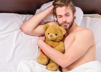 A young man waking up in bed and stretching his arms. Feet of man sleeping in comfortable bed. Sleep wake up.
