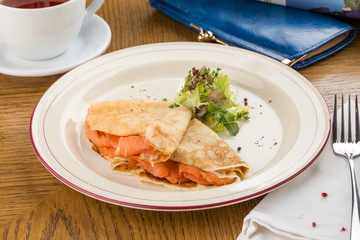 Crepes with smoked salmon on a white plate for breakfast on wooden table