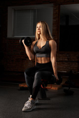 Girl fitness model posing with dumbbells in the gym. Athletic young woman posing and exercising fitness workout with weights. Shakes his biceps.