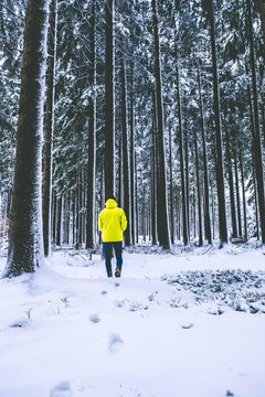 Man in yellow jacket in the winter forest