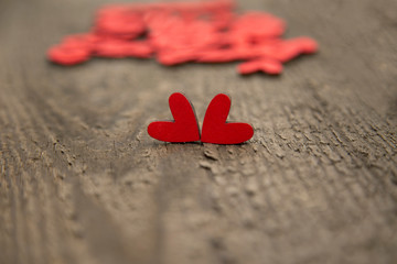 Two wooden red hearts on an old dry wooden board for Valentine's Day close-up. In the background are a handful of hearts.