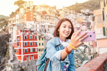 Young traveler tourist woman taking selfie on her smartphone in famous old italian village Riomaggiore, Cinque Terre, Italy