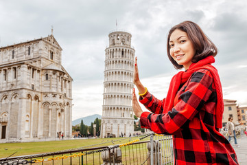 Young woman traveler making funny poses in front of the famous leaning tower in Pisa, Italy. Happy travel photos in Italy concept