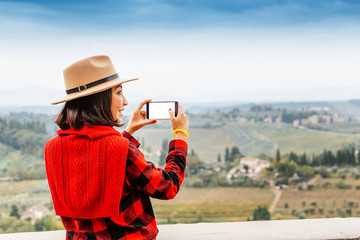 Young woman traveler with hat taking selfie with smartphone near famous Val Di Orcia valley, Tuscany, Italy