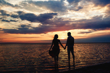 Young loving couple holding hands at sunset on the lake