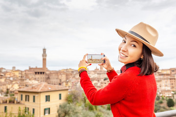 Traveler woman taking photo with her phone of the Siena city old town. Tourism in Tuscany and Europe concept